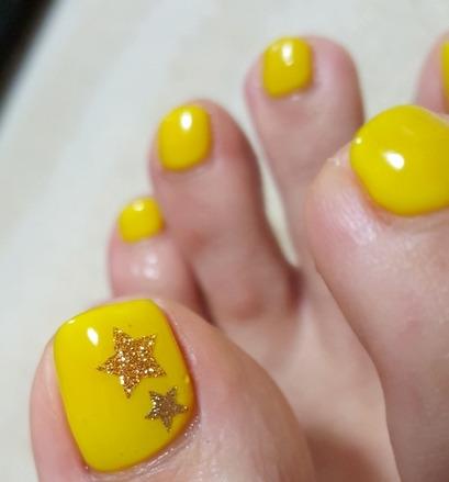 星の模様の黄色のペディキュア